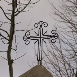 Уцелевший крест на одной из колонн ограды