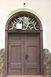 Дерев'яні двері храму з різьбленим вікном і кованими завісами